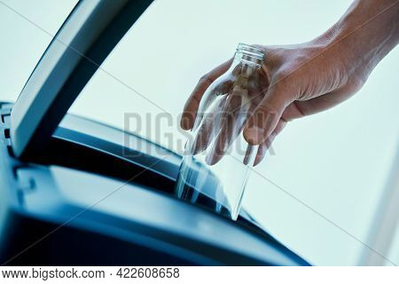 closeup of a young caucasian man throwing an empty glass bottle in the glass compartment of a home recycling bin