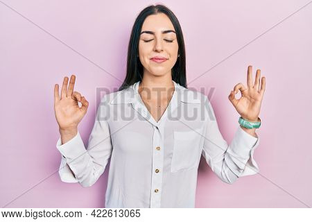 Beautiful woman with blue eyes wearing casual white shirt relax and smiling with eyes closed doing meditation gesture with fingers. yoga concept.
