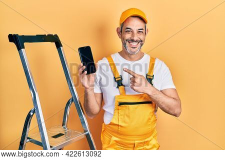 Handsome middle age man with grey hair standing by ladder showing smartphone smiling with a happy and cool smile on face. showing teeth.