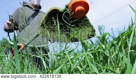 Bottom View Of A Lawn Mower In The Hands Of A Worker With Stuck Cut Grass, Close-up Of A Manual Petr