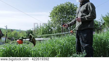 Man Mows Grass With Manual Benzo Mower, Lawn Mower With Work Tool In Green Garden Landscape, Mowing