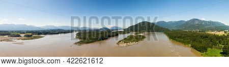Aerial Panoramic View Of A River In The Valley Surrounded By Canadian Mountain Landscape. Green Farm