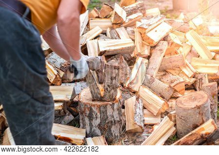 A Man Chops Wood With An Ax. Procurement Of Fuel For The Stove And Fireplace For The Winter.