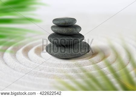 Black Stones Pile In The Sand Behind Palm Leaves. Zen Japanese Garden