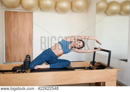 An Athletic Woman Does Body Tilts On A Reformer, Doing Pilates.