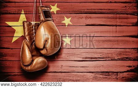Boxing gloves hanging on wooden wall with Chinese flag