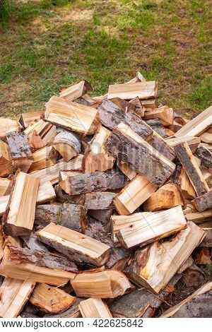 Chopped Wood In A Heap Outside, Prepared For The Winter To Heat The House. Fuel For Stove And Firepl