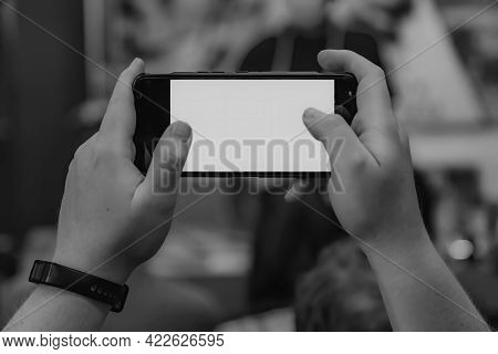 Hands Of A Man With A Fitness Tracker And Widescreen Smartphone. Black And White Photography From A