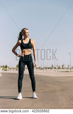 Portrait of beautiful female athlete looking away, posing with her hands on hip after intense training outdoors.