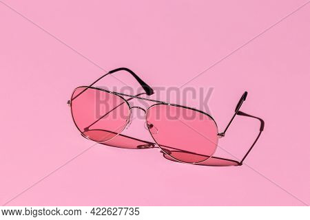 Pink Sunglasses On A Pastel Background. Hard Shadows From The Sun At Noon. Leisure, Travel And Enter