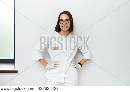 Charming Young Doctor-intern In White Medical Uniform Poses In Front Of The Camera With His Hands Ar