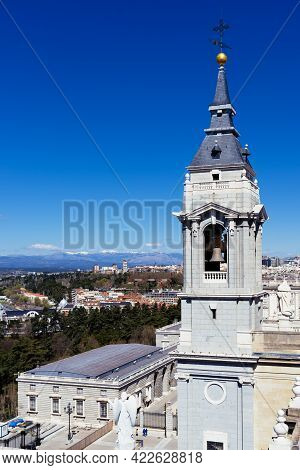 Madrid, Spain - March 20, 2021: The Belfry Of The Cathedral Of Madrid Against Cityscape A Sunny Day