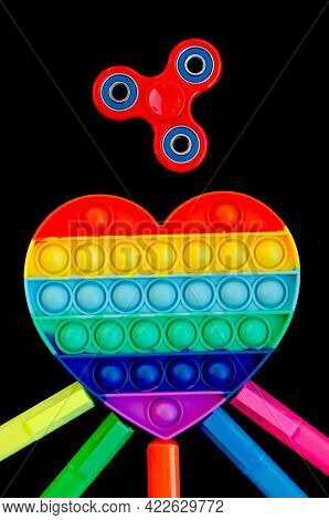 Top view of colorful anti stress sensory toy pop it rainbow heart on black background close up. And
