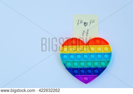 Top View Of Colorful Markers And Anti Stress Sensory Toy Pop It Rainbow Heart On Blue Background Clo
