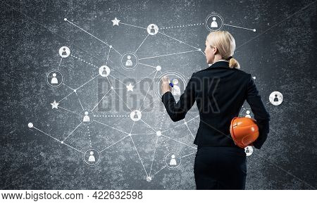 Businesswoman Pointing On Abstract Social Network. Back View Of Woman Headhunter In Business Suit An