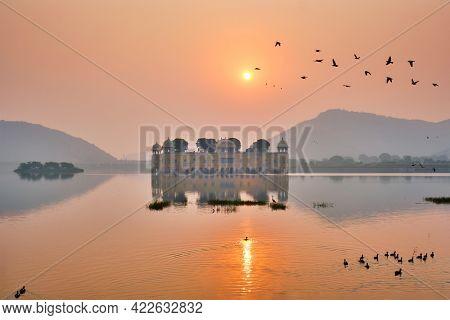 Tranquil morning at famous indian tourist landmark Jal Mahal (Water Palace) at sunrise in Jaipur. Ducks and birds around enjoy the serene morning. Jaipur, Rajasthan, India