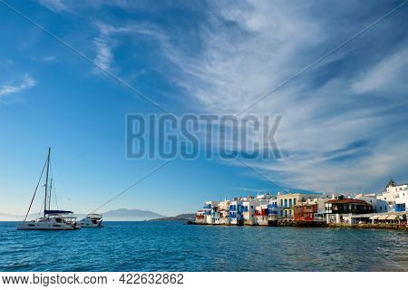 Sunset in Mykonos island, Greece with yachts in the harbor and colorful waterfront houses of Little Venice romantic spot on sunset and cruise ship. Mykonos townd, Greece