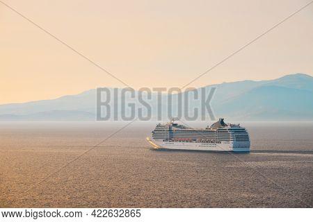 Cruise ship in Aegean sea on sunset. Mykonos island, Greece