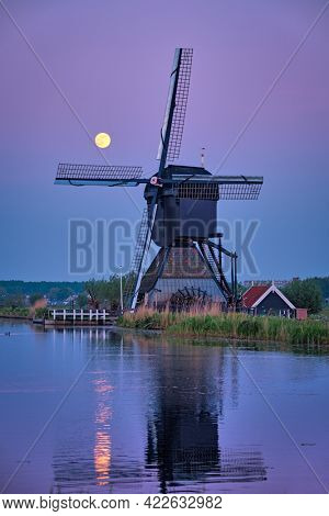 Netherlands rural lanscape with windmills at famous tourist site Kinderdijk in Holland in twilight with full moon