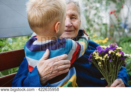 90s Years Old Senior Woman Great-grandmother Hugging Great-grandson. Kid Boy Supporting And Giving F