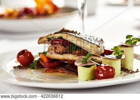 Grilled Sea Bass With Sauteed Tomatoes, Served With A Potato Ball On A White Plate, Sea Bass Fillet
