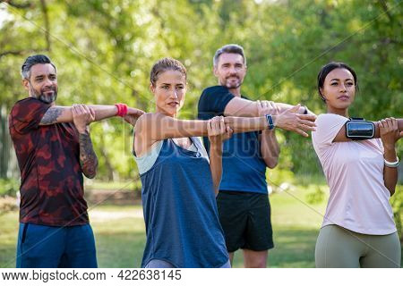 Mature woman and middle aged man stretching at park. Mid adult multiethnic group working out in park doing stretching exercise. Healthy group of mixed race friends doing stretching exercises together.