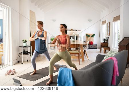 Mature woman friends practicing yoga at home. Sporty fit african woman practices yoga asana warrior pose at home with her friend. Mid adult lady practicing watching online sport lesson on tablet.