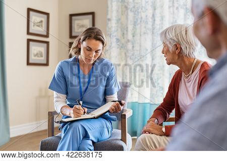 Nurse talking to old patients while being in a nursing home. Young healthcare worker visiting senior couple at care centre and writing information. Nurse in uniform noting symptoms of elderly woman.