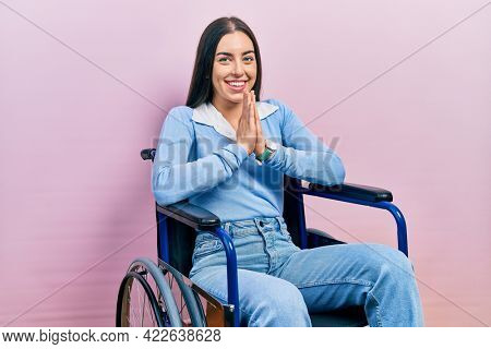 Beautiful woman with blue eyes sitting on wheelchair praying with hands together asking for forgiveness smiling confident.