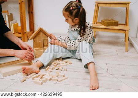 A Girl And Her Father Play A Wooden Constructor. Build A Tower Of Wooden Cubes.