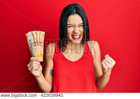 Young hispanic girl holding 500 philippine peso banknotes screaming proud, celebrating victory and success very excited with raised arm