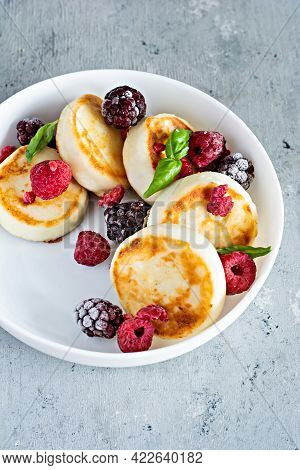 Fresh Cottage Cheese Or Ricotta  Pancakes (syrniki,fritters) On A White Plate With Fresh Berries On