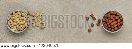 Shelled Cashews And Hazelnuts. Banner With Nuts. Nuts In A Saucer On A Stone Table Top, Top View. Pl