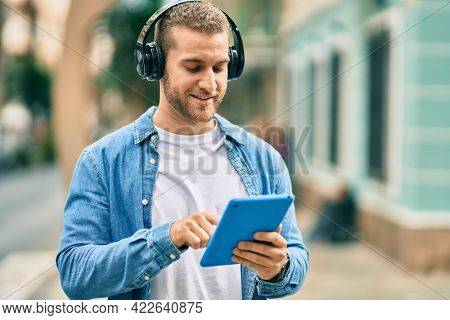 Young caucasian man smiling happy using headphones and touchpad at the city.