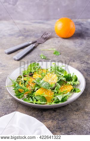 Diet Vegetarian Vitamin Salad Of Orange Pieces And Mix Of Arugula, Chard And Mizun Leaves On A Plate