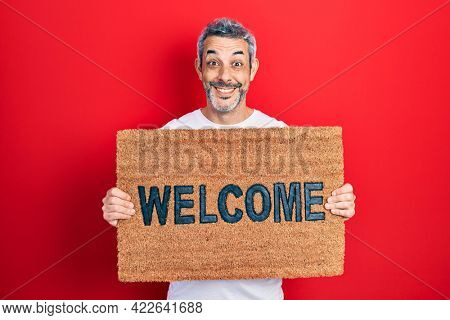 Handsome middle age man with grey hair holding welcome doormat celebrating crazy and amazed for success with open eyes screaming excited.