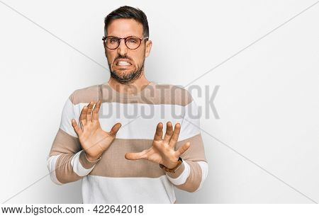 Handsome man with beard wearing casual clothes and glasses disgusted expression, displeased and fearful doing disgust face because aversion reaction.