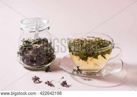 Fresh Hot Tea With Oregano In A Cup And Dry Herb In A Jar. Herbal Medicine And Alternative Therapy