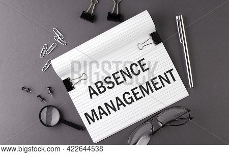 Text Absence Management On Notebook And Office Tools On Gray Desktop