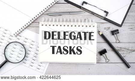 Notepad With Text Delegate Tasks With A Pen,office Tools And Graphs On Desktop.