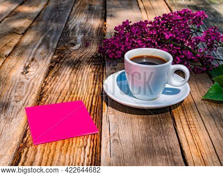 A Cup Of Coffee And A Sheet Of Paper For Notes Near A Branch Of Lilac On A Wooden Table. Coffee Drin