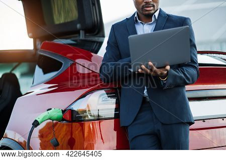 Close Up Of African American Man Holding Wireless Laptop While Leaning On His Luxury Red Car. Young