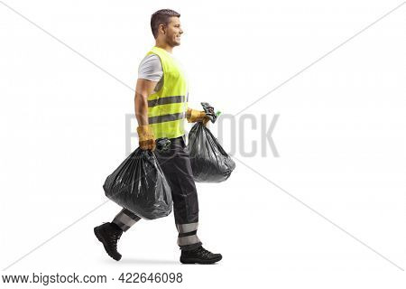 Full length profile shot of a waste collector in a uniform and gloves carrying bin bags isolated on white background