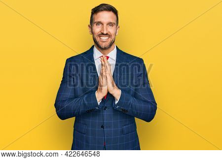 Handsome man with beard wearing business suit and tie praying with hands together asking for forgiveness smiling confident.