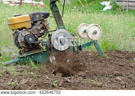 Plowing A Plot For Gardening With A Gasoline Cultivator With Special Wheels. Flying Plowed Earth Fro