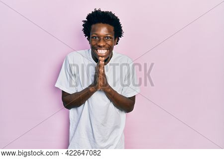 Young african american man wearing casual white t shirt praying with hands together asking for forgiveness smiling confident.