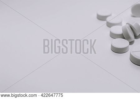 Several White Pills On A White Background In The Upper Corner Of The Photo. Black And White Photo. S
