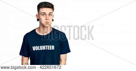 Young caucasian boy with ears dilation wearing volunteer t shirt puffing cheeks with funny face. mouth inflated with air, crazy expression.