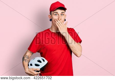 Young caucasian boy with ears dilation wearing delivery uniform and cap holding bike helmet covering mouth with hand, shocked and afraid for mistake. surprised expression