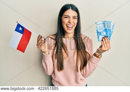 Young hispanic woman holding chile flag and chilean pesos banknotes smiling and laughing hard out loud because funny crazy joke.